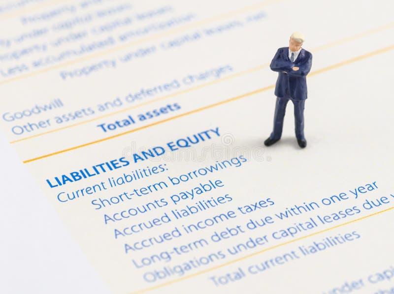 Стойка бизнесмена на балансе активов и пассивов стоковое изображение