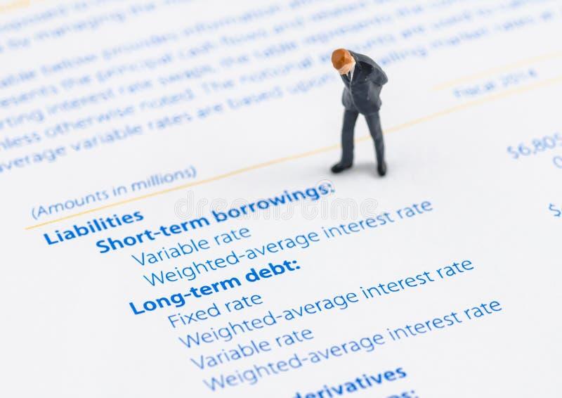 Стойка бизнесмена на балансе активов и пассивов стоковые фотографии rf