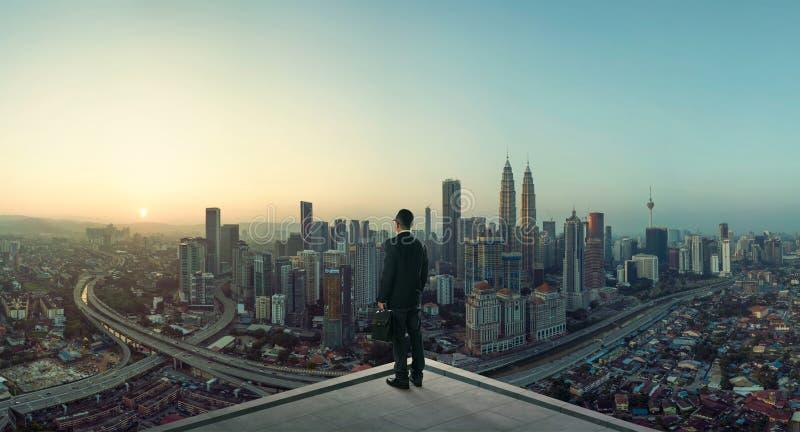 Стойка бизнесмена на крыше смотря большой взгляд городского пейзажа стоковое фото