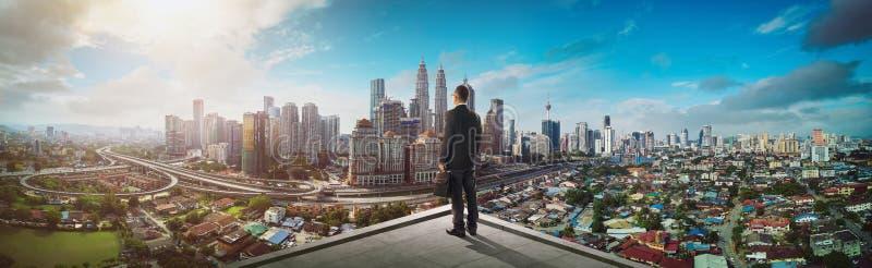 Стойка бизнесмена на крыше смотря большой взгляд городского пейзажа стоковое изображение rf