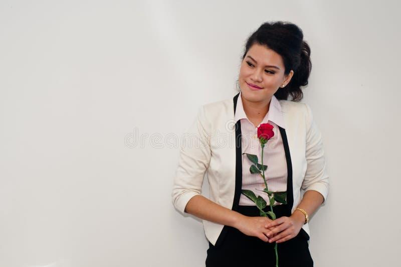 Стойка бизнес-леди и красная роза владением стоковое изображение rf