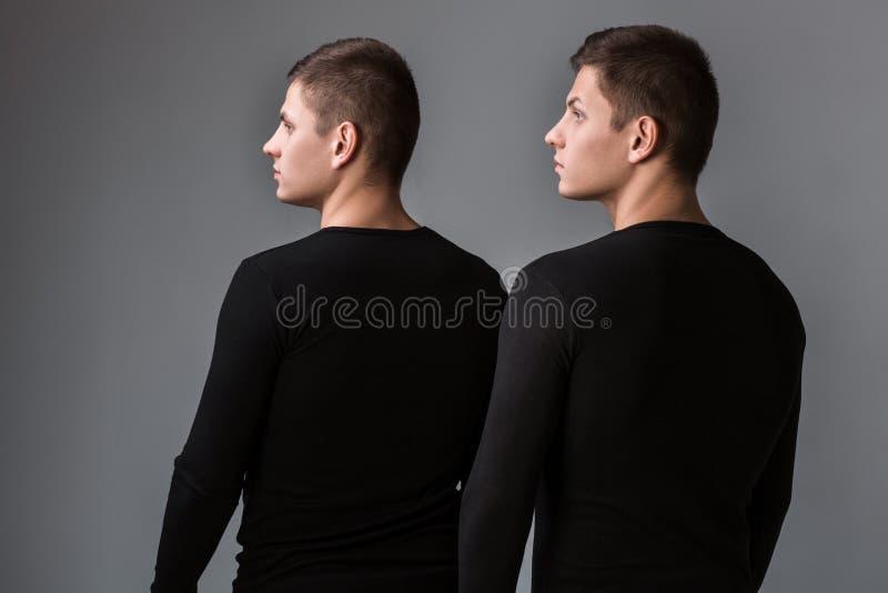 Стойка 2 брат-близнецов с их задними частями на сером backgrou стоковая фотография rf