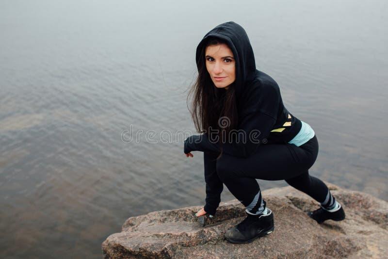 Download Стойка женщины детенышей подходящая на утесах и остатки после трудной разминки Стоковое Изображение - изображение насчитывающей ландшафт, высоко: 81805727