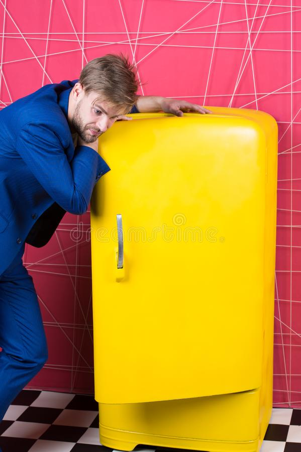 Стойка костюма человека официально элегантная около ретро винтажного желтого холодильника Винтажные бытовые приборы Холостяк голо стоковые фотографии rf