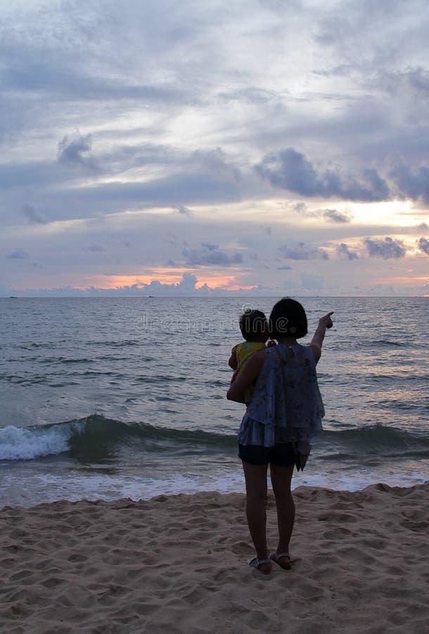 Стойка матери и дочери на пляже и взгляд в море в заходе солнца стоковая фотография