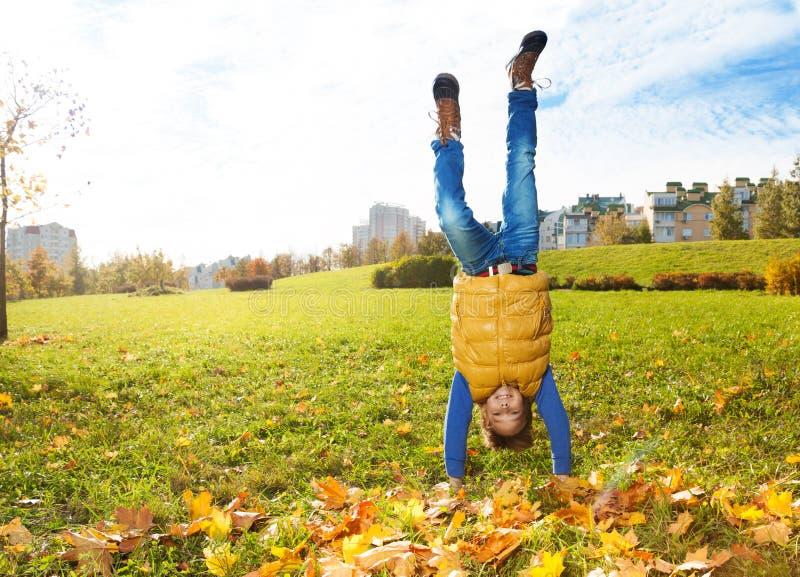 Стойка мальчика на руках на лужайке стоковые изображения