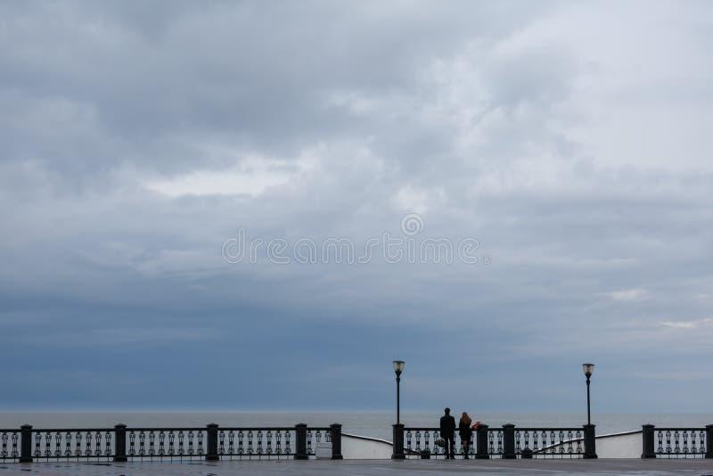 Стойка молодого человека и молодой женщины вокруг openwork загородки и взгляд на море на дождливый день стоковая фотография