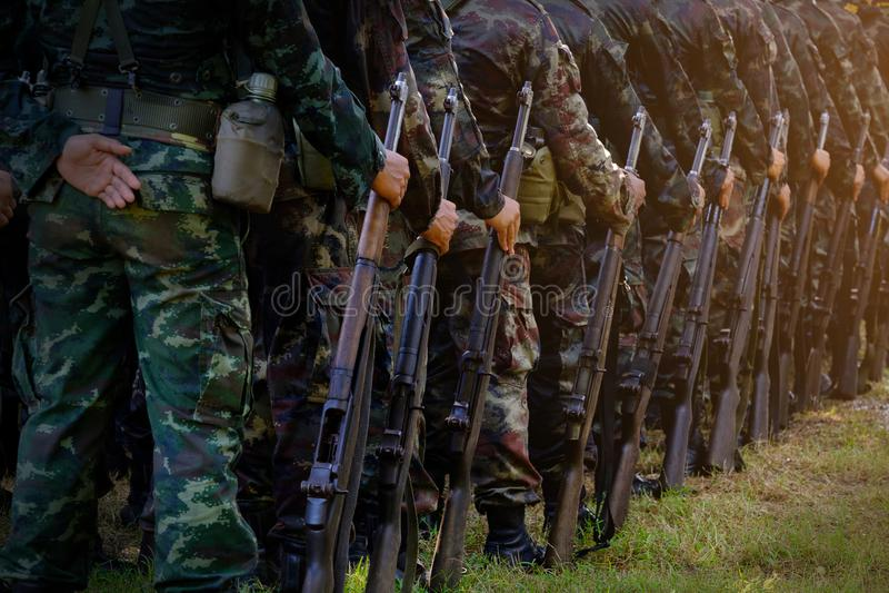 Стойка солдат в строке направлять руку пушки beretta изолировал готовый тип всхода к белизне оружия Армия, воинские линии o ботин стоковые фотографии rf