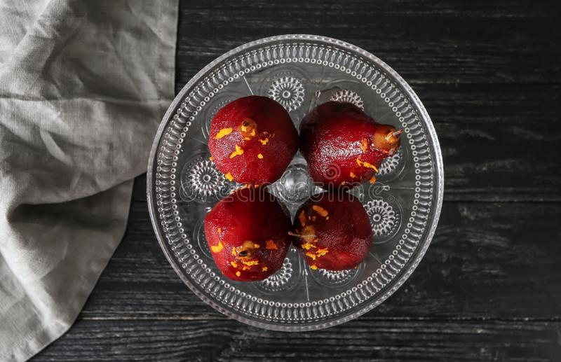 Стойка с очень вкусными краденными грушами в красном вине на деревянном столе стоковые изображения