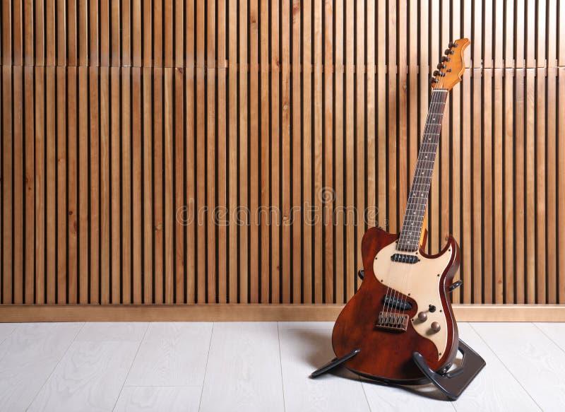 Стойка с электрической гитарой около деревянной стены стоковые фото