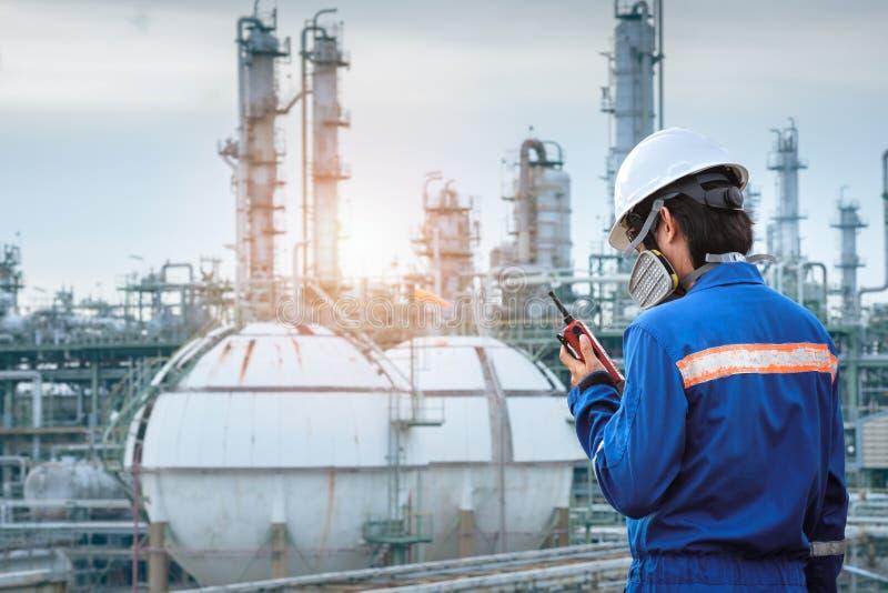 Стойка техника с маской противогаза против задней части нефтехимического завода стоковая фотография