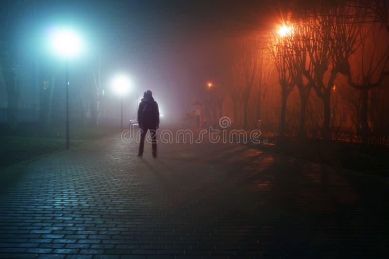 Стойка человека самостоятельно на туманной улице стоковое фото rf
