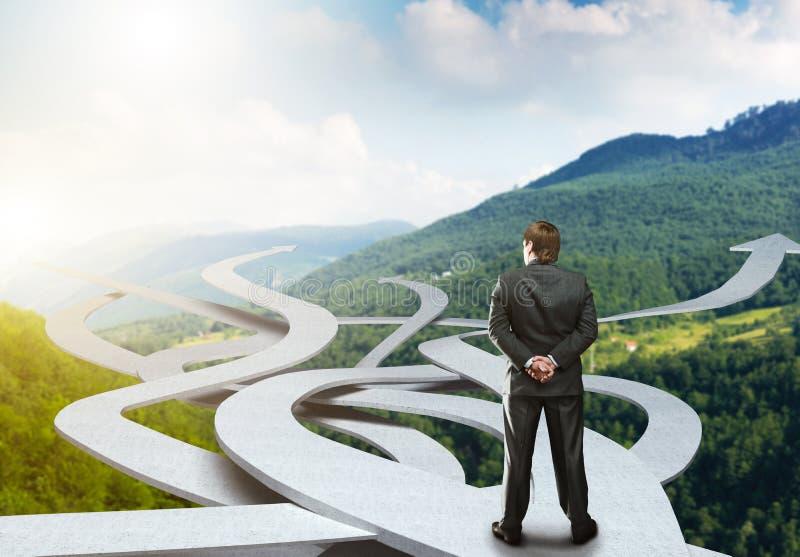 Стойки бизнесмена выбирая его путь стоковая фотография rf
