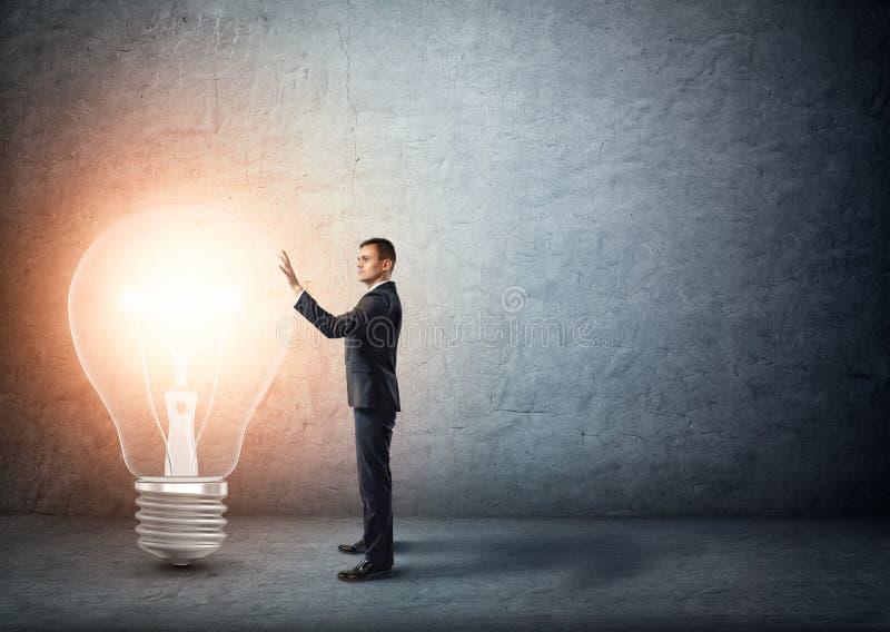 Стойки бизнесмена касаясь большой накаляя электрической лампочке стоковые фото