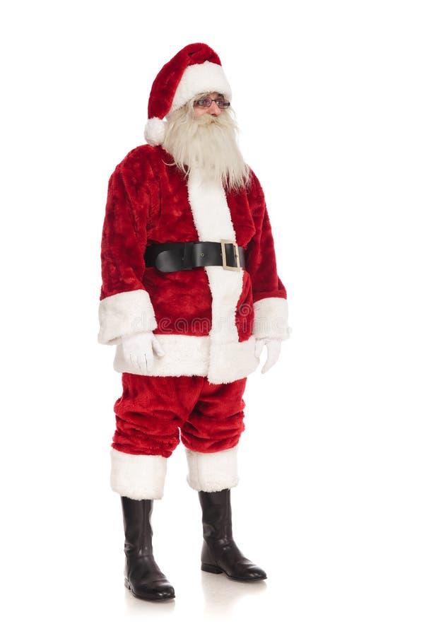 Стойки и взгляды стекел Санта Клауса нося, который нужно встать на сторону стоковая фотография rf