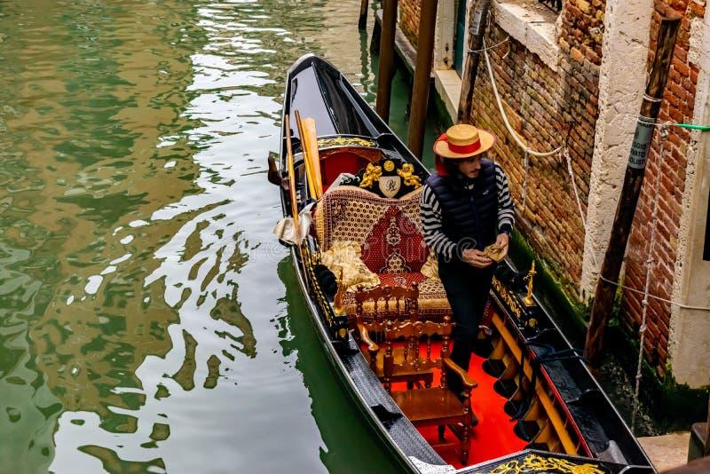 Стойки соломенной шляпы привлекательного молодого итальянского Gondolier нося в традиционной гондоле с роскошным оформлением стоковые фотографии rf