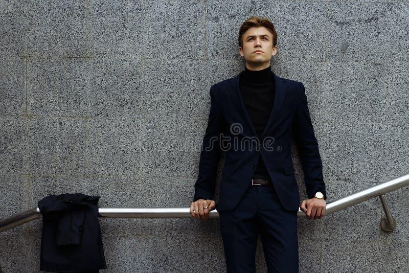 Стойки человека полагаясь на стене на перилах, на улице Тоскливость и забота Расстроенный парень стоковая фотография