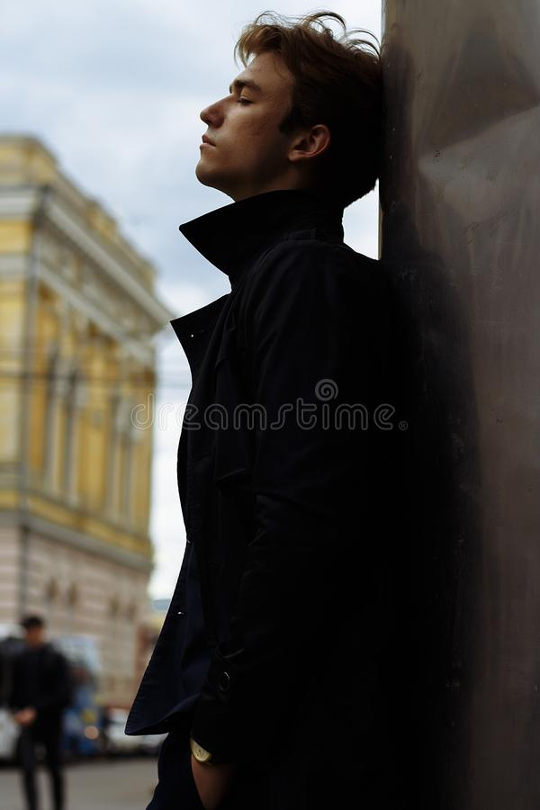 Стойки человека полагаясь на стене, на улице с его глазами закрыли ветер надувает его волосы, тоскливость и заботу стоковые изображения