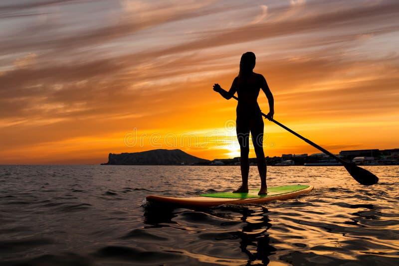 Стойте вверх восхождение на борт затвора на тихом море с теплыми цветами захода солнца лета стоковое изображение