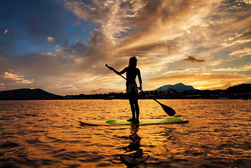 Стойте вверх восхождение на борт затвора на тихом море с теплыми цветами захода солнца лета стоковое фото