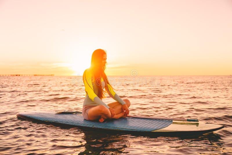 Стойте вверх восхождение на борт затвора на тихом море с цветами захода солнца Женщина ослабляет на доске маленького глотка стоковые фото