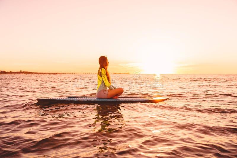 Стойте вверх восхождение на борт затвора на тихом море с цветами захода солнца Женщина на доске МАЛЕНЬКОГО ГЛОТКА стоковые фото