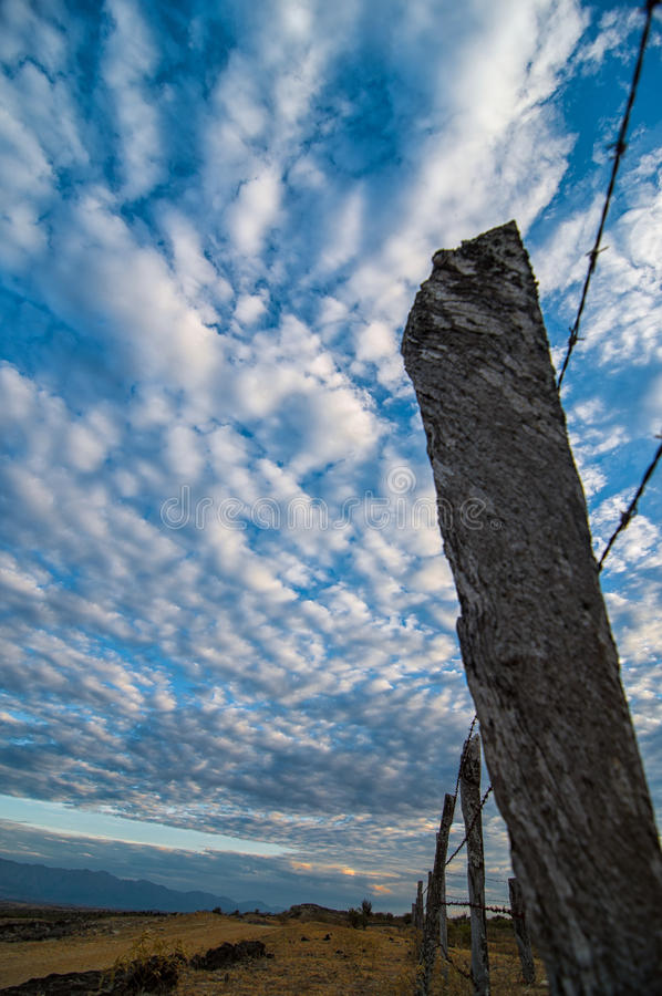 Столб загородки и драматическое небо стоковые изображения rf