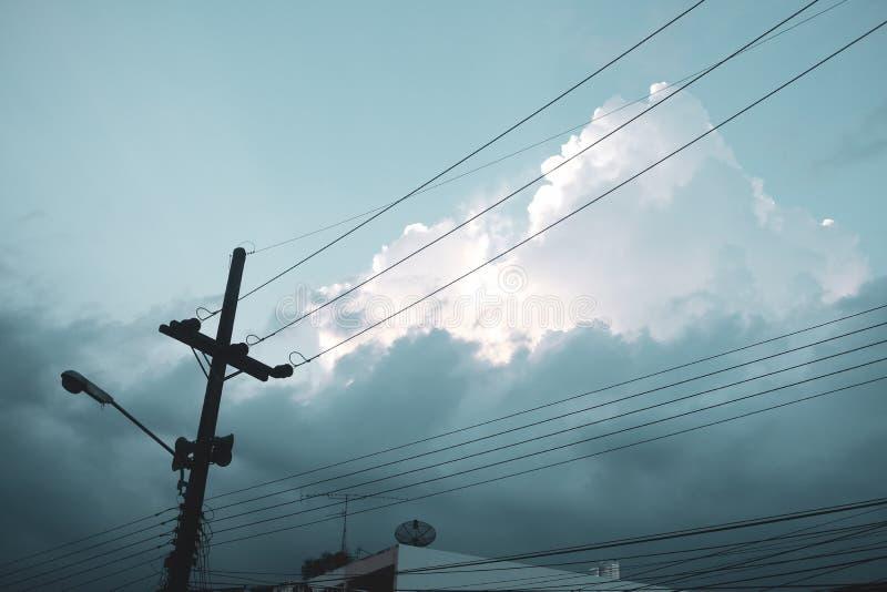 Столб и облачное небо электричества Взгляд низкого угла стоковые фото