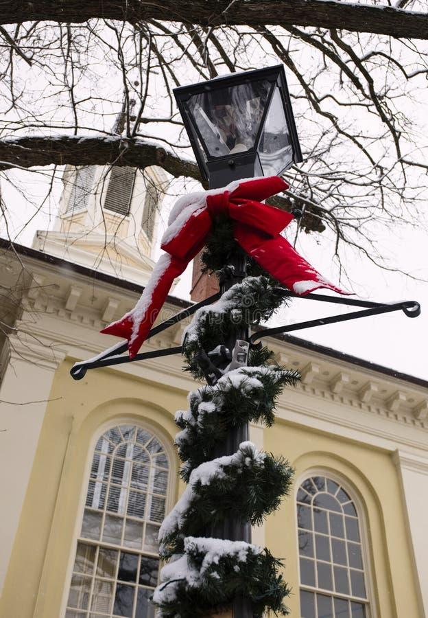 Столб лампы украшенный с растительностью и красный смычок для рождества с снегом в Warrenton, Вирджинии стоковое изображение