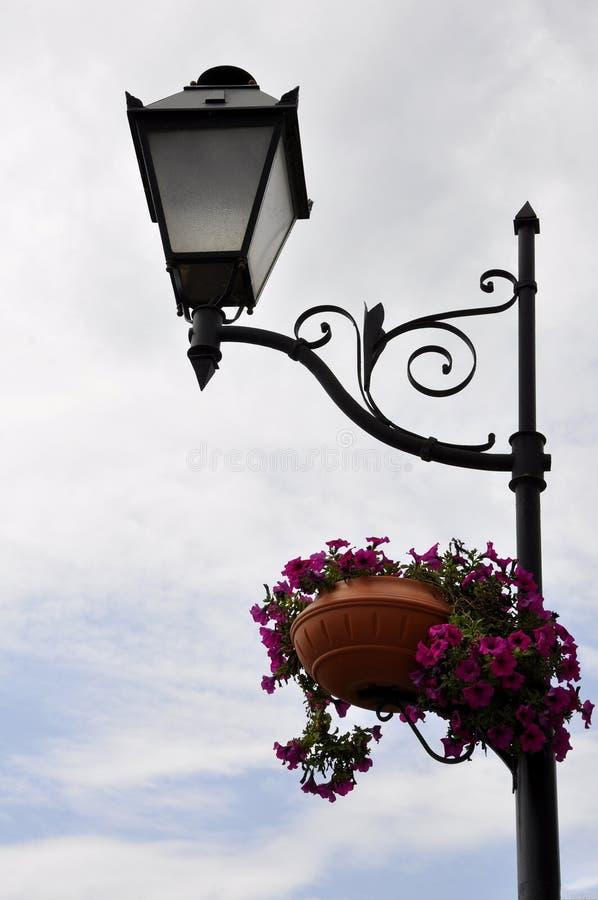 Столб лампы уличного света с корзинами красных цветков стоковые фотографии rf