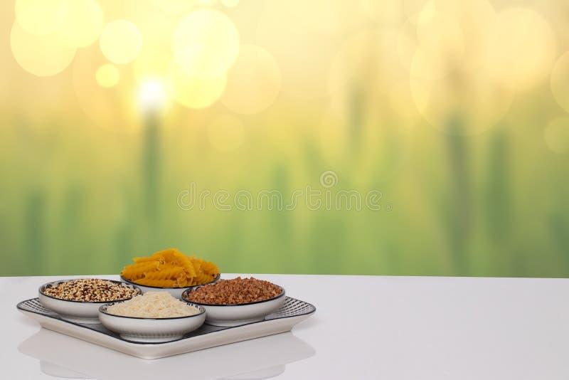Столешница на предпосылке еды овоща 4 шара с гречихой, лапшами, рисом и квиноа на белой таблице над абстрактное ярким стоковые изображения rf