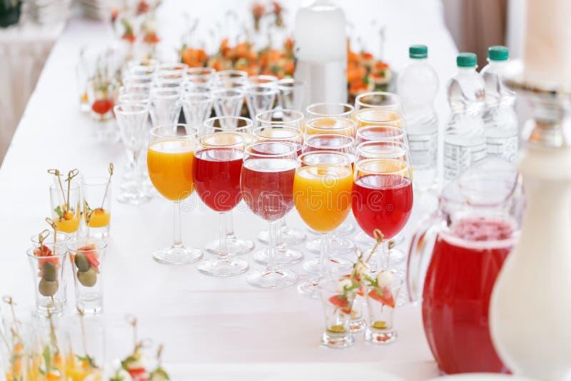 Столешница полная сока не алкогольных напитков стекел стекел, апельсинового сока, воды и ягоды s с канапе и стоковое фото rf