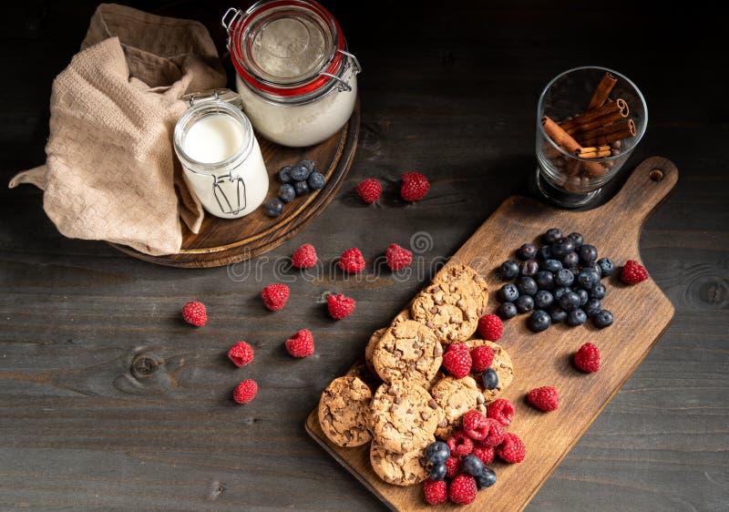 Столешница штабелировала печенья и ягоды шоколада рядом с ручками молока и циннамона стоковое изображение