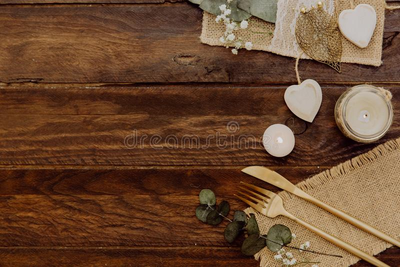 Столовый прибор с мешковиной и украшениями Деревенская свадьба установленная на деревянную предпосылку стоковое фото rf