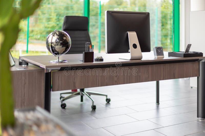 Столы расположены в современном меблированном офисе стоковая фотография rf