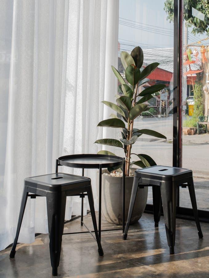 Столы, стулья из стали с растительными горшками, украшенные белыми шторами и штукатурный пол, или в стиле Лофта Дизайн интерьера стоковые изображения rf