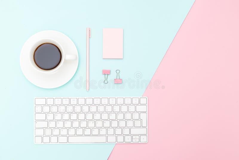 Стол и розовые канцелярские принадлежности дальше на предпосылке пастельного цвета Скопируйте курорт стоковые изображения rf