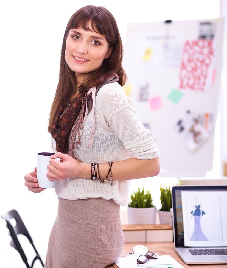 Стол молодого привлекательного модельера готовя в офисе, держа чашку стоковое изображение rf