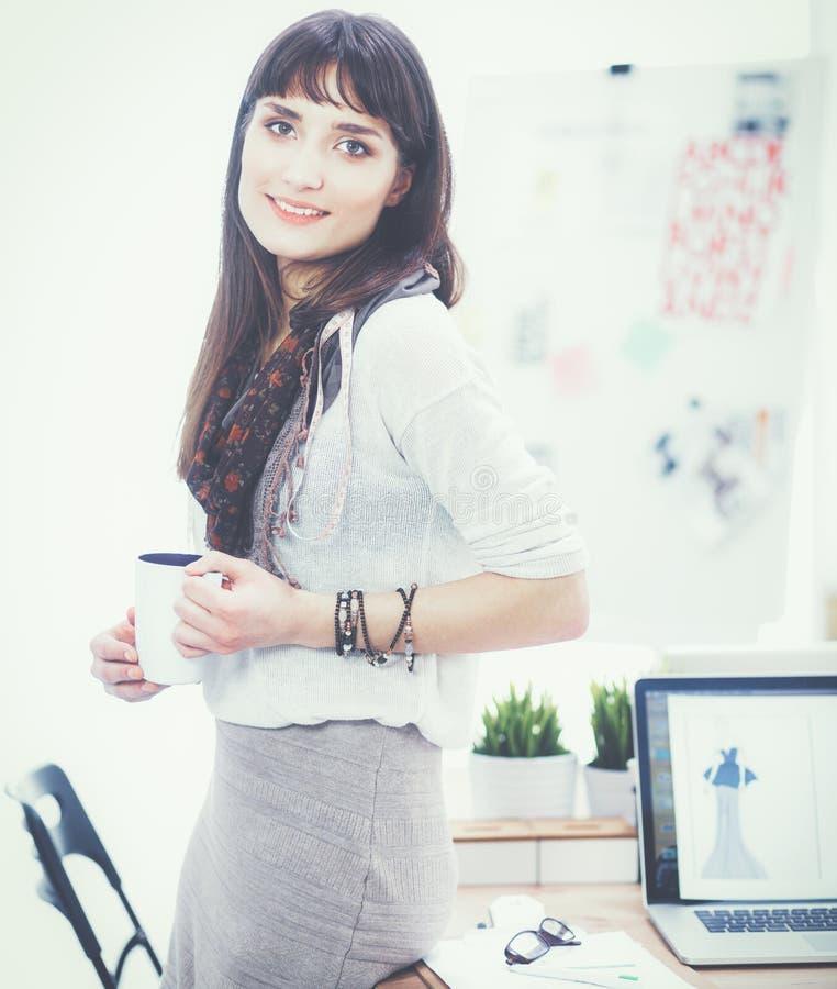 Стол молодого привлекательного модельера готовя в офисе, держа чашку стоковая фотография