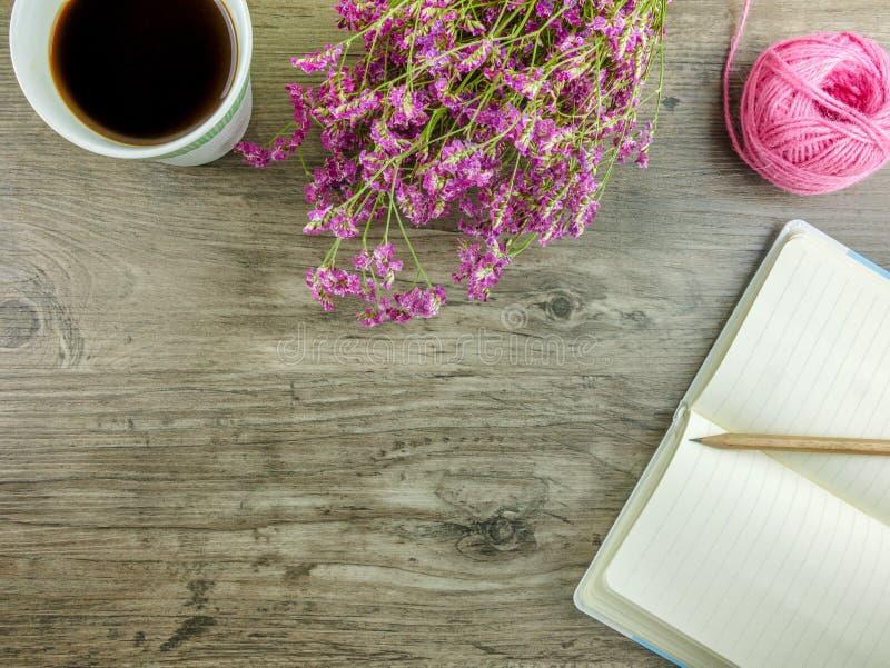 Стол положенный квартирой серый деревянный с канцелярскими принадлежностями, цветками и кофе стоковое фото rf