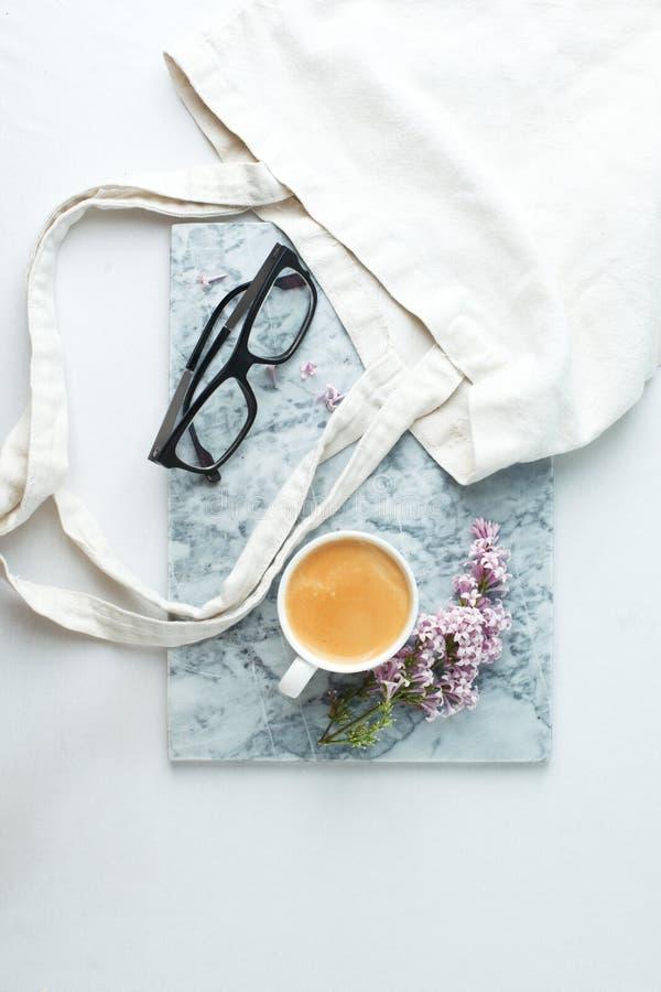 Стол стиля мрамора блога моды с аксессуаром женщины: чашка кофе, ветви сирени гуглит и нул сумок ткани отхода на белизне стоковые изображения