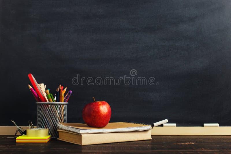 Стол учителя с материалами сочинительства, книгой и яблоком, пробелом для текста или предпосылкой для темы школы скопируйте космо стоковое фото