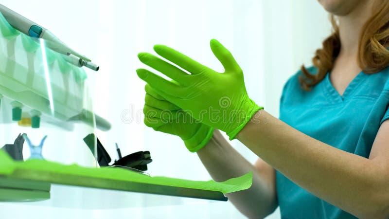 Стоматологическая медсестра нося зеленые защитные перчатки, высококачественное обслуживание стоковые фотографии rf