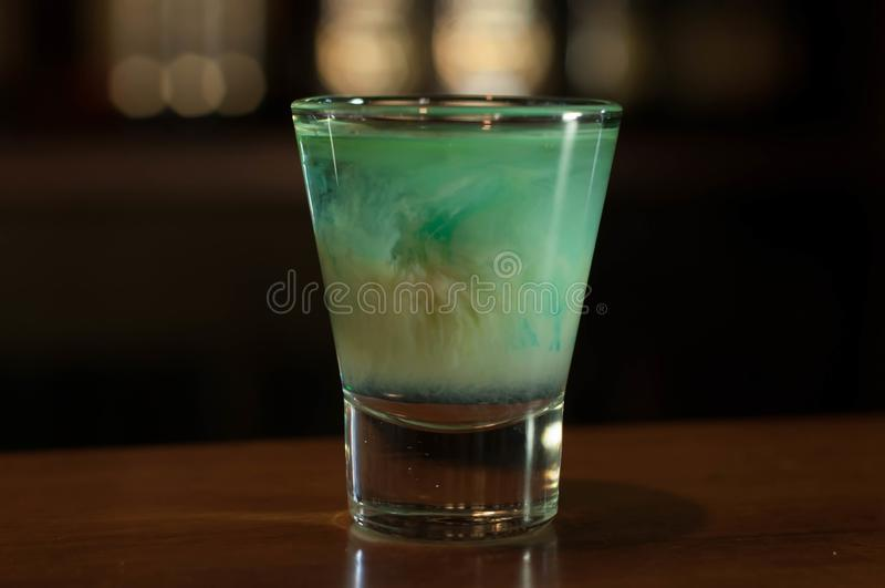 Стопка с голубым напитком алкоголя на деревянном столе в баре стоковое изображение