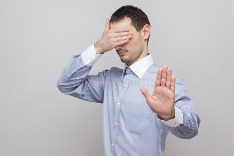 Стоп, я не хочу видеть это Красивый бизнесмен щетинки в голубом положении рубашки, покрывая его глаза и преграждая с руками остан стоковое фото