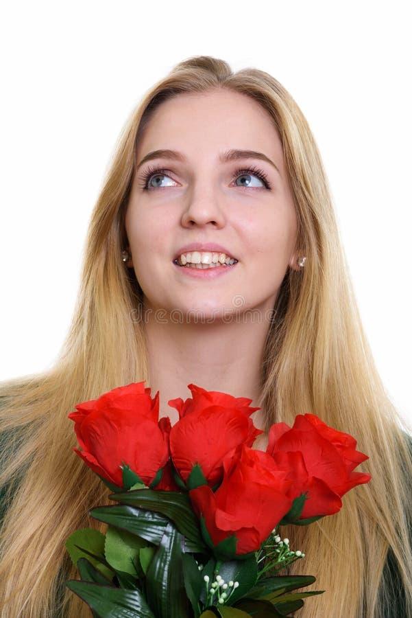 Сторона внимательного счастливого девочка-подростка усмехаясь пока держащ красный цвет стоковая фотография