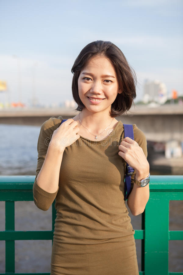 Сторона головной съемки усмехаясь азиатской женщины при рюкзак стоя вне стоковое изображение rf