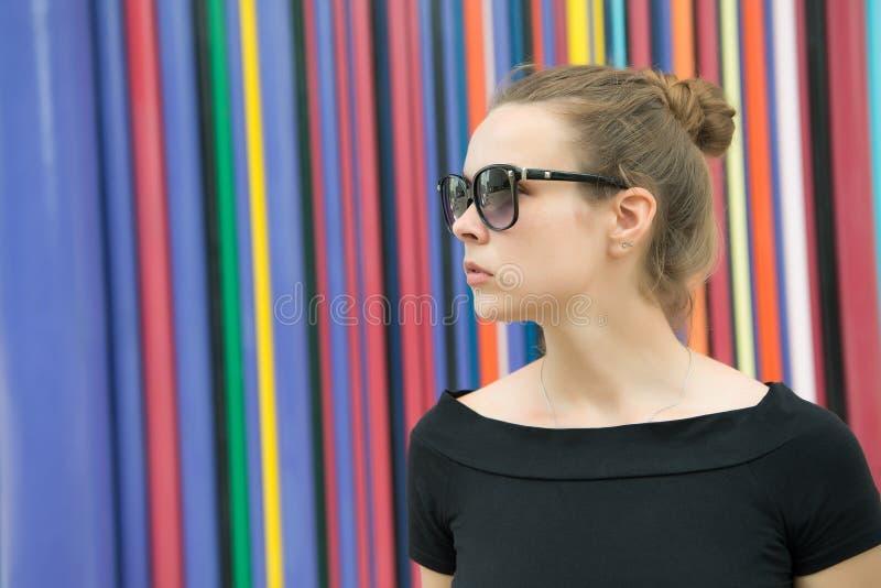 Сторона дамы нежная загадочная с черными eyeglasses перед striped красочной стеной в Париже Возникновение женщины стильное стоковое изображение