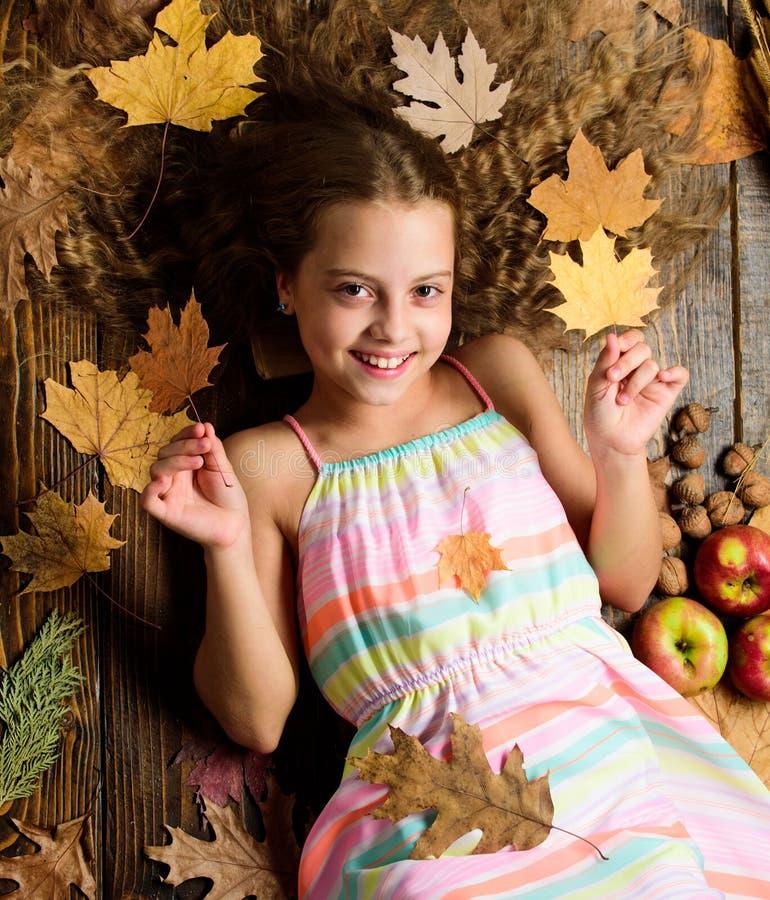 Сторона девушки ребенк усмехаясь кладет деревянные атрибуты падения предпосылки Ребенок с длинными волосами с упаденными кленовым стоковые изображения