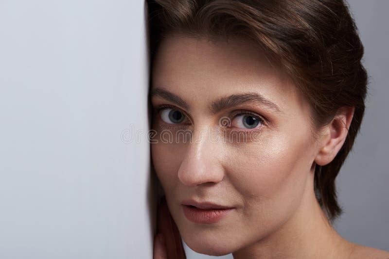 Сторона женщины постная к белой стене стоковое фото